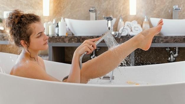 Mulher com vista lateral relaxando na banheira