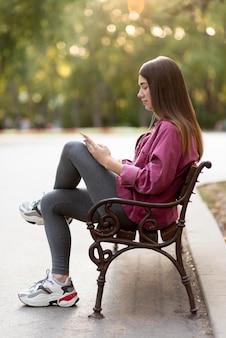 Mulher com vista lateral relaxando no banco