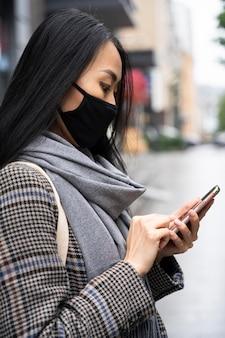 Mulher com vista lateral segurando um smartphone