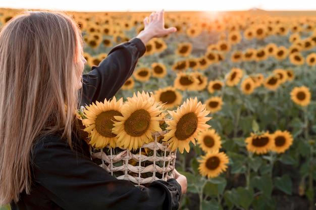Mulher com vista lateral segurando uma cesta de flores