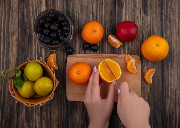 Mulher com vista superior corta laranja em uma tábua com ameixas em uma cesta e ameixas cereja em uma jarra com fundo de madeira
