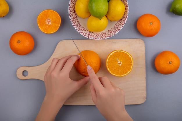 Mulher com vista superior corta laranjas em uma tábua com limões e limas em um prato sobre fundo cinza