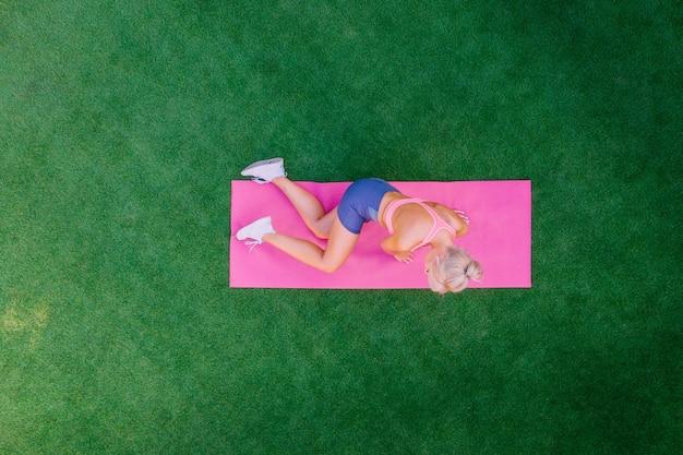 Mulher com vista superior fazendo exercícios enquanto estava deitada na grama verde em um dia de verão.