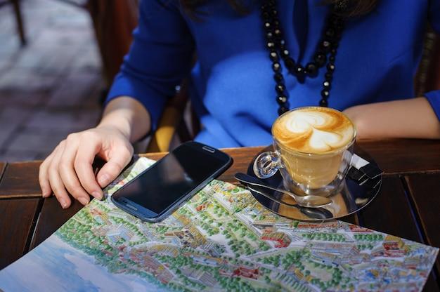 Mulher, com, xícara café, esperto, telefone, e, mapa