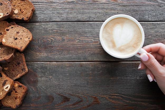 Mulher com xícara de cappuccino perto de fatias de pão de centeio