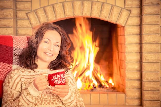 Mulher com xícara perto da lareira. conceito de férias de inverno