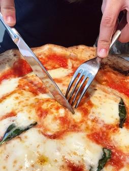 Mulher come com faca e garfo uma pizza margherita