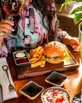 Mulher come hambúrguer servido com batata frita, ketchup e maionese