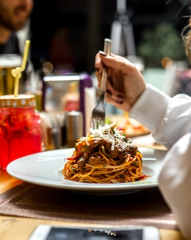 Mulher come macarrão espaguete com carne verduras parmesão vista lateral