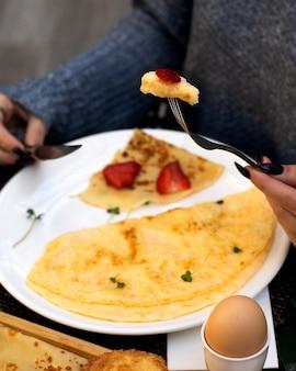 Mulher come omelete e crepe com morangos