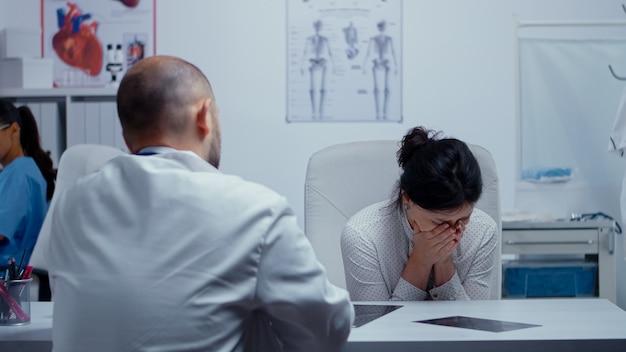 Mulher começa a chorar no médico após ouvir más notícias sobre a saúde dela ou de outra pessoa querida. más notícias sobre paciente terminal. câncer ou outro conceito de doença terminal