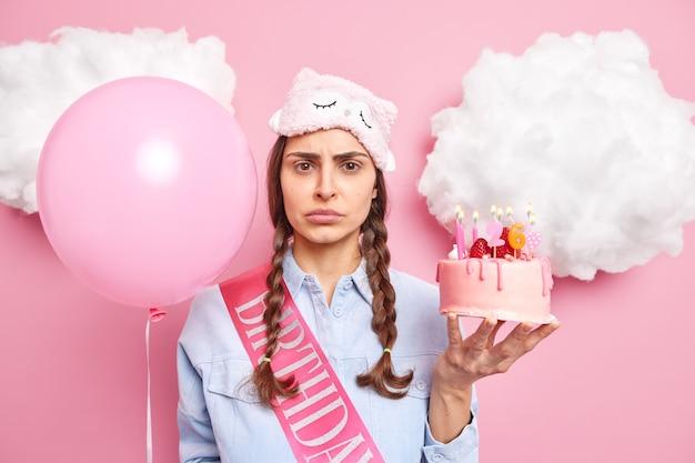 Mulher comemora 26 anos sozinha segurando bolo de morango e um balão inflado vestida com roupas casuais domésticas isoladas em rosa