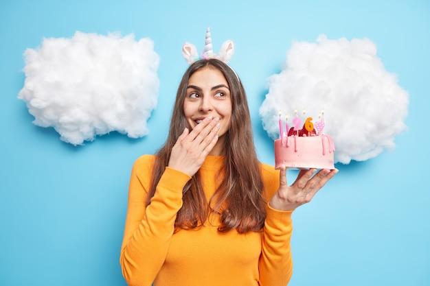 Mulher comemora aniversário segurando bolo de morango contra boca e rindo, vestida com um macacão casual isolado no azul
