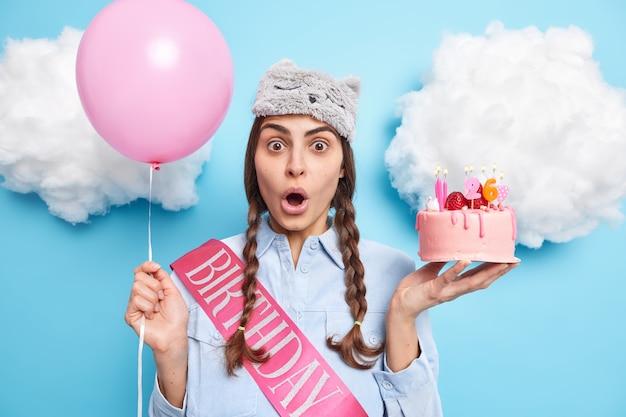 Mulher comemora poses de aniversário com bolo e balão inflado mantém a boca aberta vestida com camisa e máscara de dormir na cabeça em poses contra o azul