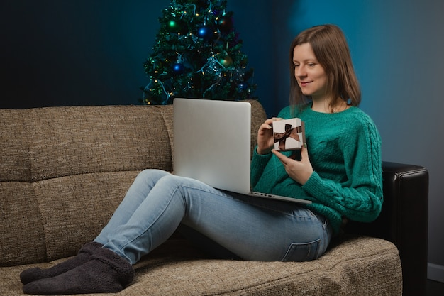 Mulher comemorando a véspera de natal com parentes por chamada online no laptop
