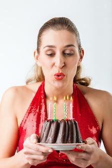 Mulher comemorando aniversário com bolo soprando velas