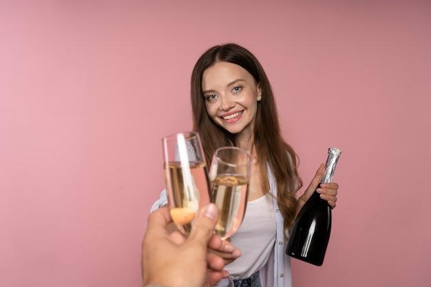 Mulher comemorando com garrafa de champanhe e taças