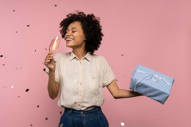 Mulher comemorando com taça de champanhe e presente