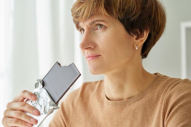 Mulher comendo barra de chocolate e não sente cegueira do receptor do paladar devido ao coronavírus