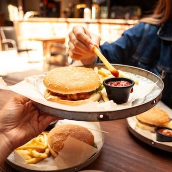 Mulher comendo batata frita com ketchup