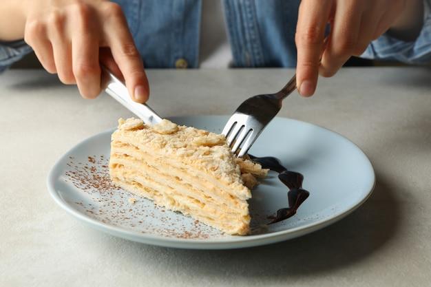 Mulher comendo bolo delicioso de napoleão