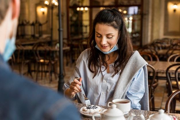 Mulher comendo bolo no restaurante