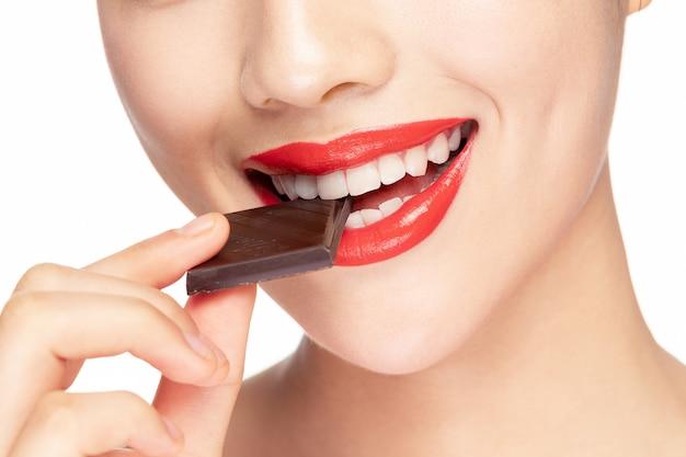 Mulher comendo chocolate boca closeup