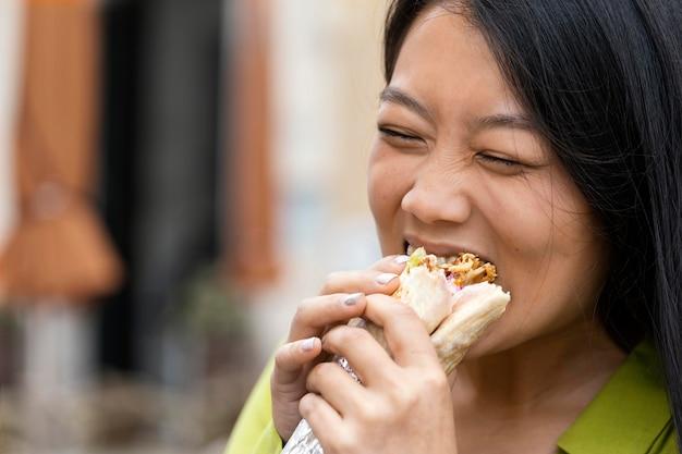 Mulher comendo comida de rua ao ar livre
