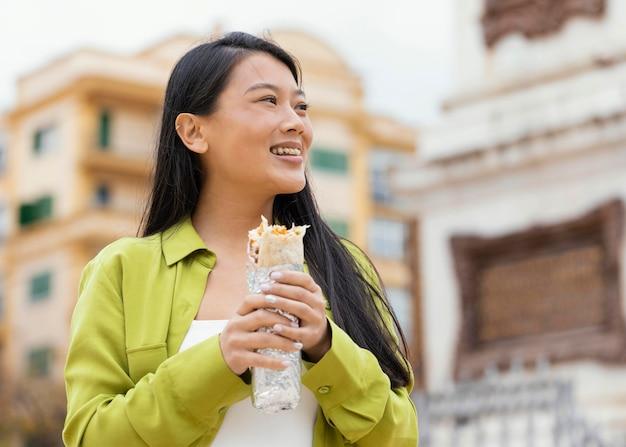 Mulher comendo comida de rua