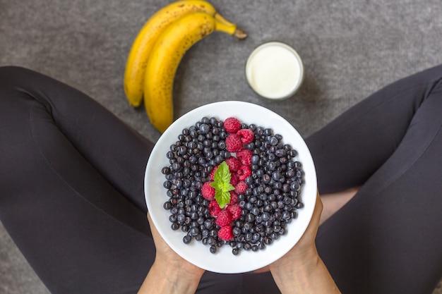 Mulher comendo comida saudável. yong garota no esporte vestir segurando um prato de berris frescos. bananas e produtos lácteos no