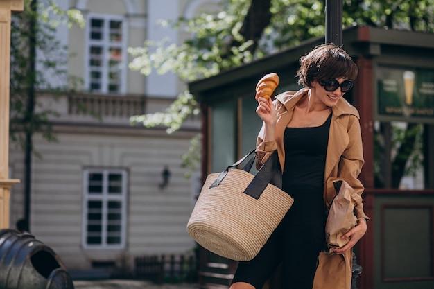 Mulher comendo croissants fora da rua