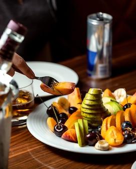 Mulher comendo damasco do prato de frutas de maçã, cereja, pêssego, pêra, uva