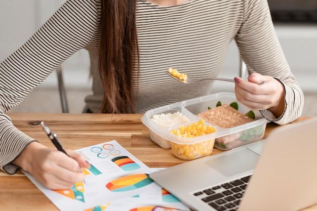 Mulher comendo e trabalhando em casa