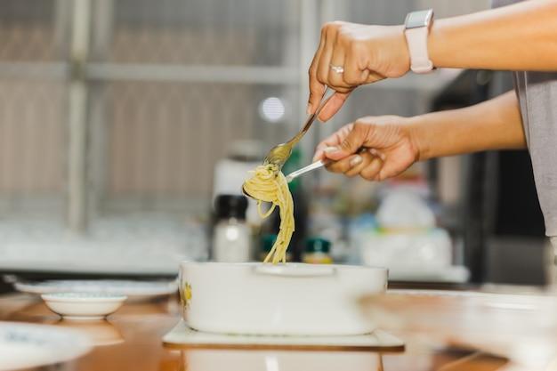 Mulher comendo espaguete cremoso à carbonara com garfo e colher na mesa de jantar