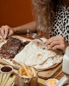 Mulher comendo fatias de bife dentro do pão sírio