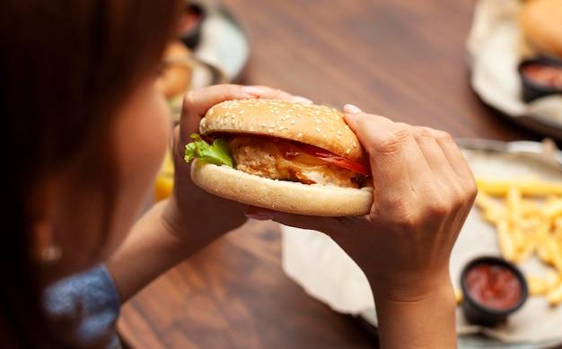 Mulher comendo hambúrguer em ângulo alto