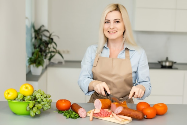 Mulher comendo linguiça na cozinha
