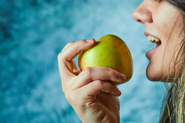 Mulher comendo maçã na parede azul.