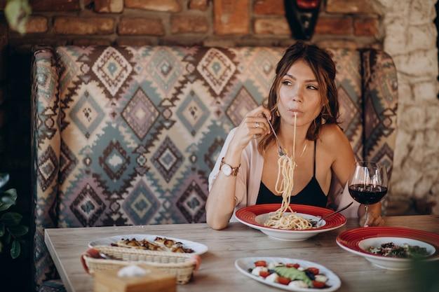 Mulher comendo macarrão em restaurante italiano
