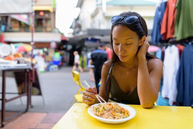 Mulher comendo macarrão pad thai na estrada khao san