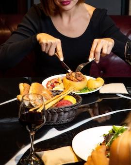 Mulher comendo marmelo assado recheado no restaurante