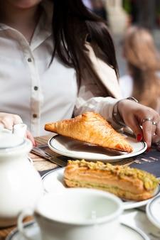Mulher comendo massa no café da manhã