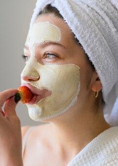 Mulher comendo morango enquanto usava máscara facial