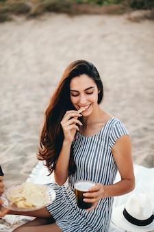 Mulher comendo nacho en la playa