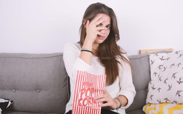 Mulher comendo pipoca e assistindo a filmes.
