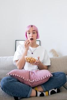 Mulher comendo pipoca enquanto olha um videogame