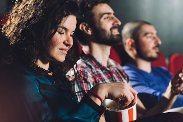 Mulher comendo pipoca saborosa no cinema Foto gratuita