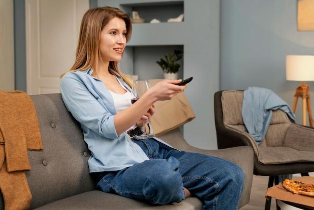 Mulher comendo pizza enquanto assiste tv