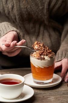 Mulher comendo pudim de caqui. mulher tomando café da manhã com smoothie de caqui com creme de iogurte e chocolate