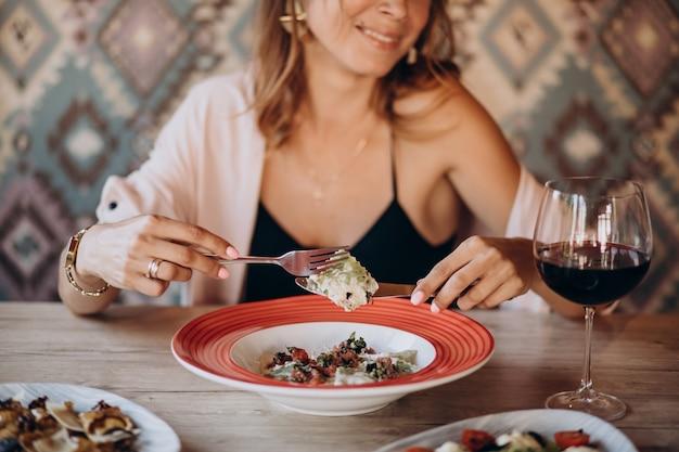 Mulher comendo ravióli em restaurante italiano